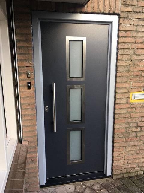 Kunststof voordeur met buitenzijde RvS rand vleugeloverdekkend Antraciet nerf, met zilvergrijs nerf. Gemonteerd te Roosendaal