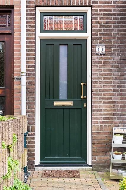 Traditionele groene kunststof voordeur met glas in lood bovenlicht
