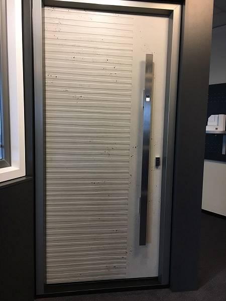 Voordeur in betonlook in Nordic profiel. Greep met fingerprintslot.